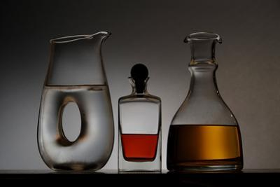 A Modern Glass Pitcher of Water, a Carafe of White Wine and a Bottle with Brandy