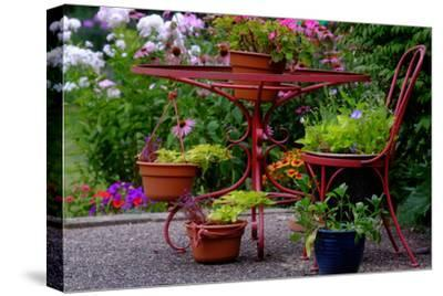A Red Wrought Iron Plant Stand Displaying Flowers and Plants