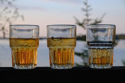Three Glasses of Brandy Old Fashions on the Railing of a Wooden Deck