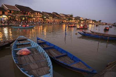Boats moored on the Thu Bon River opposite Bach Dang Street in the old town of Hoi An, Vietnam