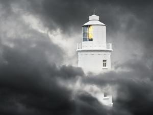 Lighthouse Emerging From Dark Clouds by Paul Hardy