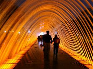 People Walking Through One of the 13 Illuminated Fountains at El Parque De La Reserva by Paul Kennedy
