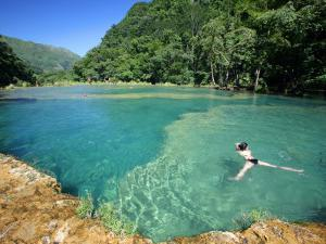 Visitors Swimming in Turquoise-Coloured Waters of Semuc Champey by Paul Kennedy