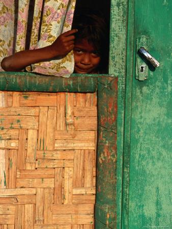 Young Child Peeking Out from Behind Curtain at Watukarare, Sumba, East Nusa Tenggara, Indonesia