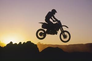 Motocross Rider in Silhouette against Sunset Sky by Paul Nevin