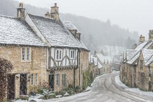Looking down the quintessential English village of Castle Combe in the snow, Wiltshire, England, Un by Paul Porter