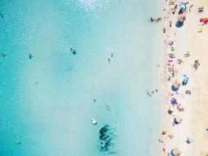 Aerial View of Sandy Beach with Tourists Swimming in Beautiful Clear Sea Water by paul prescott