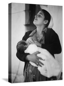 Israeli Mother Breast Feeding Her Baby by Paul Schutzer
