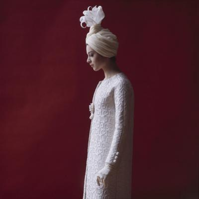 Model Dressed in a White Turban, Gloves, and Brocade Coat by Yves St Laurent, Paris, France, 1962