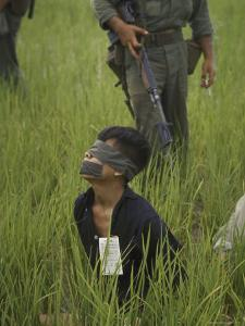 Viet Cong Prisoner Being Guarded by Marines, Mouth and Eyes Taped to Prevent From Calling for Help by Paul Schutzer