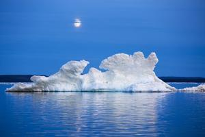 Canada, Nunavut, Moon Rises Behind Melting Iceberg in Frozen Channel by Paul Souders
