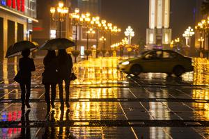 China, Chongqing, Pedestrians Walking with Umbrellas Along the Street by Paul Souders