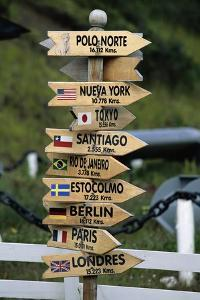 Mileage Sign Pointing Directions in Puerto Williams by Paul Souders