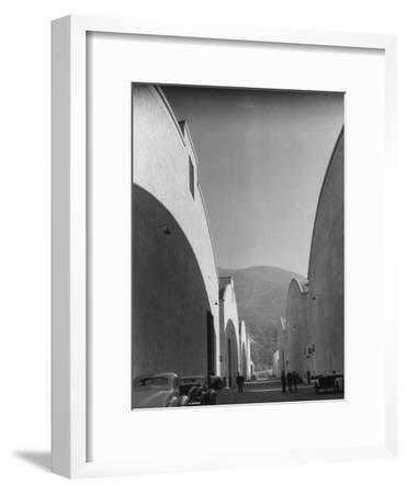 People Walking Between Sound Stages at Warner Bros. Studio-Margaret Bourke-White-Framed Premium Photographic Print