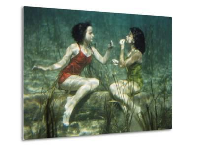Performing swimmers put on lipstick underwater-J^ Baylor Roberts-Metal Print