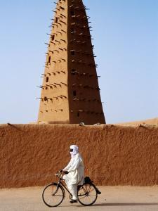 Robed Tuareg Man Cycling Past Minaret of Mud-Brick Grande Mosquee, Agadez, Niger by Pershouse Craig