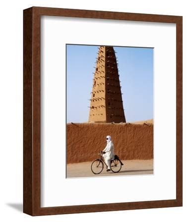 Robed Tuareg Man Cycling Past Minaret of Mud-Brick Grande Mosquee, Agadez, Niger