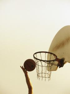 Person's Hand Holding a Basketball Near the Hoop