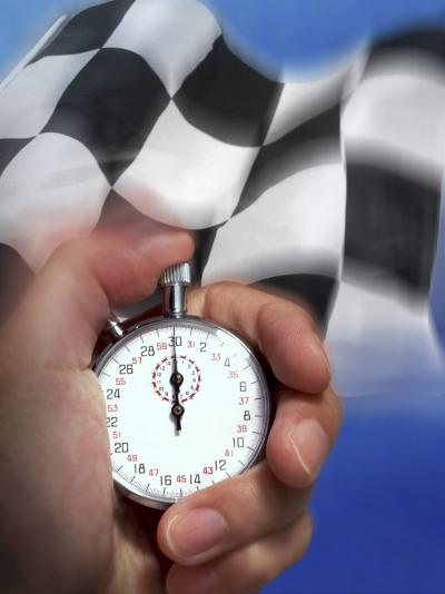 Person's Hand Holding a Stopwatch in Front of a Checkered Flag--Photographic Print