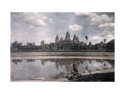 Person Sits by a Moat Which Surrounds the Towers of Angkor Vat-Gervais Courtellemont-Photographic Print
