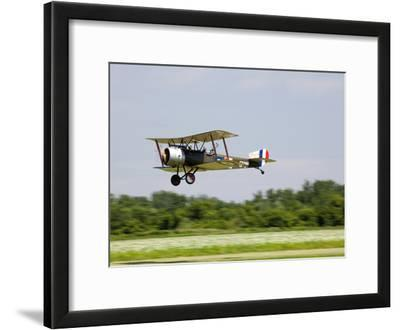 A Sopwith 1-1/2 Strutter Flies Low over a Grass Runway