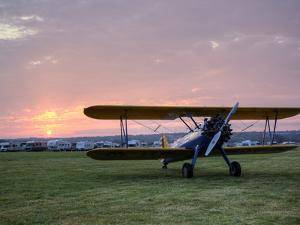A Stearman Biplane on a Grass Airfield at Dawn by Pete Ryan