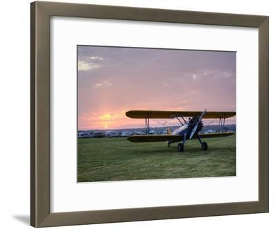 A Stearman Biplane on a Grass Airfield at Dawn