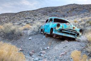 Remains of an Old Vehicle in a Desert Landscape by Pete Ryan