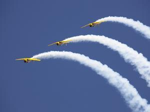 Three Yellow Planes Leave Arcs of White Smoke Behind by Pete Ryan