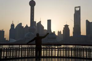 Man Doing Morning Exercises and City Skyline, Shanghai, China by Peter Adams