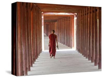 Monk in Walkway of Wooden Pillars To Temple, Salay, Myanmar (Burma)