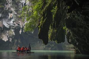 A Boatman Guides Tourists Down the Poxin River as it Emerges from Underground by Peter Carsten