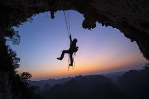 A Climber Descends the Great Arch of Chuanzhang Cave at Sunset by Peter Carsten