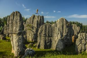 A Climber Jumps Atop a Spire in the Stone Forest by Peter Carsten