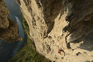 A Climber Scales the Great Arch of Chuanzhang Cave by Peter Carsten