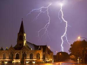 Cloud to Ground Lightning Strikes Sever the Sky Above a Church by Peter Carsten