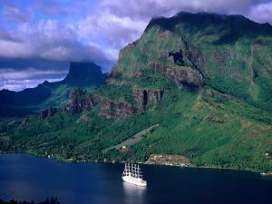 A Sailboat Cruises Past Mountainous Shoreline, Moorea, Society Islands, The, French Polynesia by Peter Hendrie