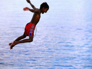 Boy Falling into Water, Lifou Island, Loyalty Islands, New Caledonia by Peter Hendrie