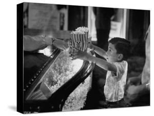 Boy Buying Popcorn at Movie Concession Stand by Peter Stackpole