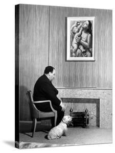 British Born Film Director Posing Beside Fireplace at Home with Pet Sealyham Terrier, Mr. Jenkins by Peter Stackpole