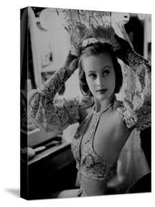 Chorus Girl Hope Chandler Securing Her Feathered Headdress as She Sits at Makeup Table by Peter Stackpole