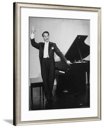 Comedian Pianist Victor Borge, in White Tie and Tails, Standing at Piano and Making Funny Faces