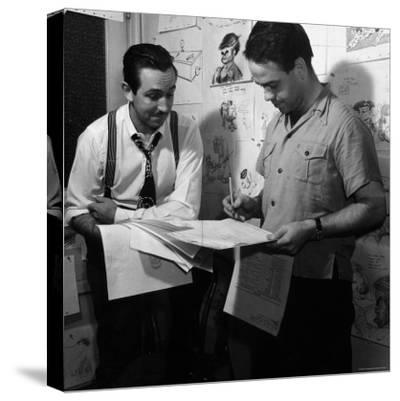 """Director Walt Disney Looking over Sketches from His Latest Picture """"Pinocchio."""""""
