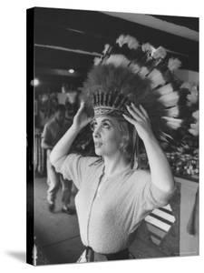 Gina Lollobrigida Trying on Native American Head Piece by Peter Stackpole