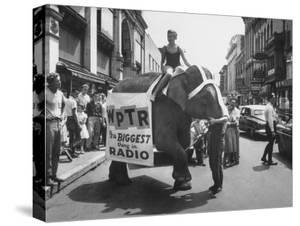 Girl Riding Elephant as a Publicity Stunt for a Radio Station by Peter Stackpole