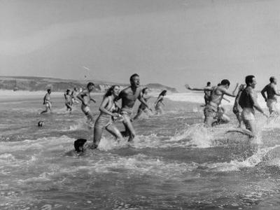 Lifeguards and Members of Womens Swimming Team Start Day by Charging into Surf