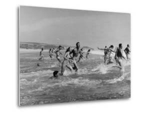 Lifeguards and Members of Womens Swimming Team Start Day by Charging into Surf by Peter Stackpole