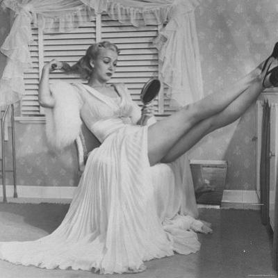 Movie Actress Carole Landis in Negligee as she Brushes Her Hair, Showing Off Gorgeous Legs