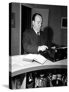Movie Director Alfred Hitchcock Typing Script on a Portable Typewriter by Peter Stackpole