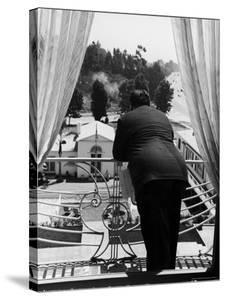 Suit Clad Movie Director Alfred Hitchcock as He Leans on Balcony Railing of Apartment by Peter Stackpole